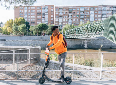Happy young man in casual wear prepares with his electric scooter next to a bridge in a city
