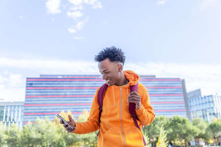 Dark skinned boy with wide smile looks at his mobile phone in front of a building
