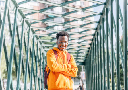 Smiling man in casual wear and orange tracksuit poses with crossed arms on a metal bridge Archivio Fotografico