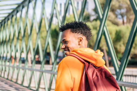 Happy boy with dark skin in tracksuit and with backpack walks on a green bridge