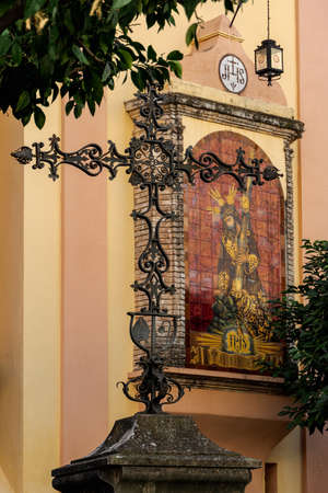 Sevilla, Andalusia / Spain. Jan 06, 2019 : Forged iron cross with tree and Ceramic altarpiece dedicated to Señor de la Salud de San Roman in the facade of the Sanctuary of the Gypsies, Triana. Editorial