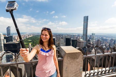 uptown: ?Girl taking selfies with view to Uptown Manhattan