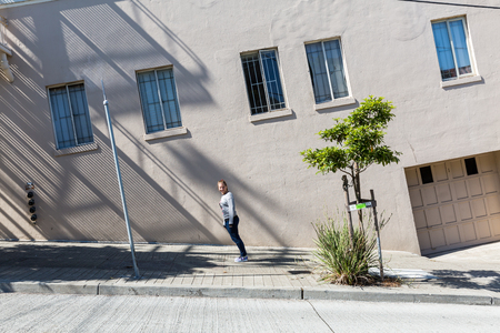 lean over: Girl standing on a steep road in San Francisco Stock Photo