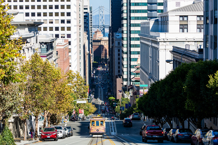 frisco: SAN FRANCISCO, CALIFORNIA - SEPTEMBER 17: View of the California Street in direction Downtown in San Francisco on September 17, 2015. This view provides a look to the Bay Bridge and the cable cars.