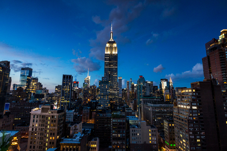 NEW YORK - AUGUST 23: View to Midtown Manhattan with the famous Empire State Building at sunset on August 23, 2015. This view is from the rooftop of the 230-fifth Bar.