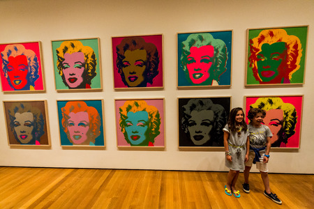 NEW YORK, MUSEUM OF MODERN ART - AUGUST 23: A girl stands in the front of the famous Marilyn Monroe picture from Andy Warhole in the Museum of Modern Art in New York an August 23, 2015. Redakční