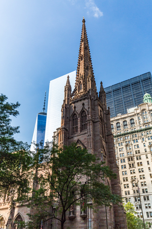 broadway tower: NEW YORK - AUGUST 24: Views of the Trinity Church between the Skyscrapers in Manhattan Downtown, New York on August 24, 2015. This church was constructed in 1698.