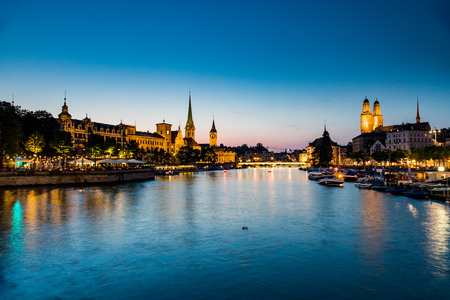 grossmunster cathedral: ZURICH, SWITZERLAND - JULY 4: Famous postcard view of various houses and churches in the old town part of Zurich at sunset on July 4, 2015. Zurich is the biggest city in Switzerland.