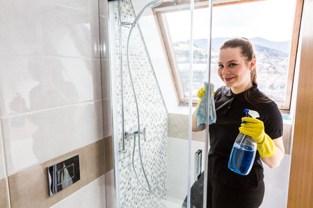 female in douche: Member of housekeeping staff at work in bathroom Stock Photo