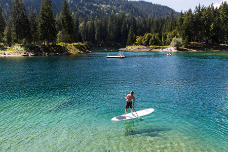 swimm: View of a man on a paddleboard at Caumasee in Switzerland Stock Photo