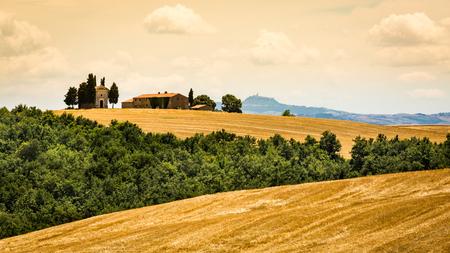 SAN QUIRICO D ORCIA, ITALIA - 16 DE JULIO DE 2016: Vista de una casa e iglesia de la granja en la región toscana San Quirico d Orcia en Italia el 16 de julio de 2016. Esta región es popular para los motivos fotográficos del estilo toscano. Editorial