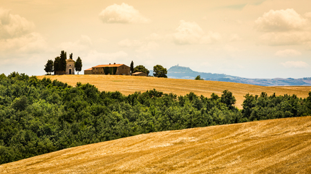 SAN QUIRICO D ORCIA, ITALY - JULY 16, 2016: View of a farm house and church in the tuscan region San Quirico d Orcia in Italy on July 16, 2016. This region is popular for tuscan style photographic motives. Editorial