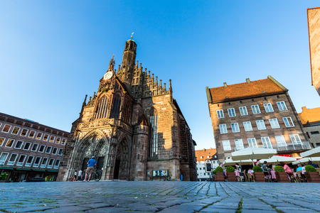 NURENBERG, GERMANY - JUNE 22, 2016: Exterior view of the Frauenkirche and historical building around in the old town part of Nurnberg on June 22, 2016. Its on the eastern side of the main market