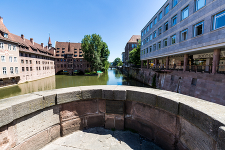 NUREMBERG, GERMANY - JUNE 23, 2016: View from a historical arch bridge called Museumsbrucke to the Heilig Geist Hospital in the old town part of Nurnberg on June 23, 2016.