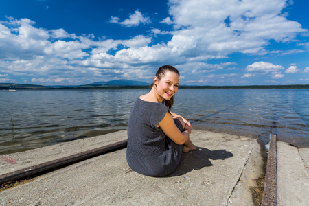 sitting on the ground: View of a girl at the barrier lake Oravska Priehrada in northern Slovakia