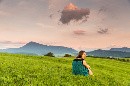 View of a girl watching the sunset on a meadow and the Mountain Choc in background in Slovakia