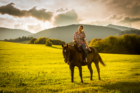 View of a girl with a blue and red mapped shirt with a horse in Slovakia Stock Photo