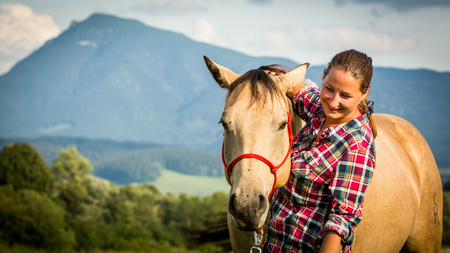 appaloosa: View of a girl with a blue and red mapped shirt with a horse in Slovakia Stock Photo