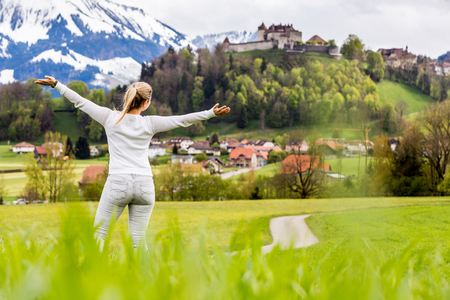 White dressed beautiful blonde girl on a meadow in front of the Grueyeres Village in the Swiss canton of Fribourg.