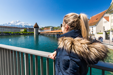 View of a young tourist girl in the front of the Lucerne Chapel Bridge (Kapellbrucke)
