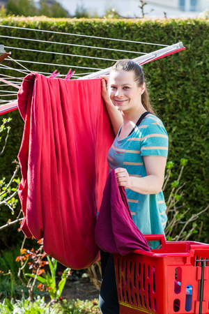 Girl is hanging the washed red sheets up in the garden