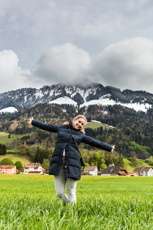 Beautiful blonde girl on a meadow in front of the Grueyeres Village in the Swiss canton of Fribourg. Stock Photo