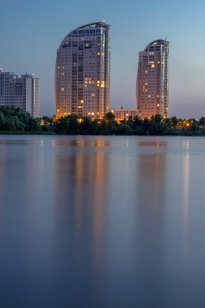 dniper: Night city buildings reflected in river water. Vertical. HDR.