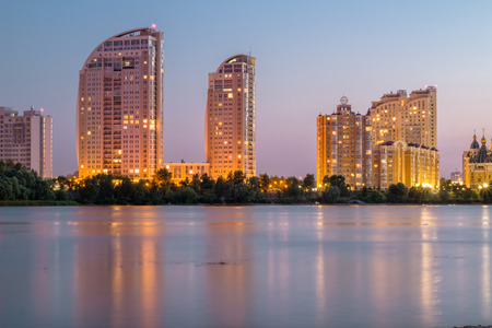dniper: Lightened buildings reflected in river water. Evening city. HDR
