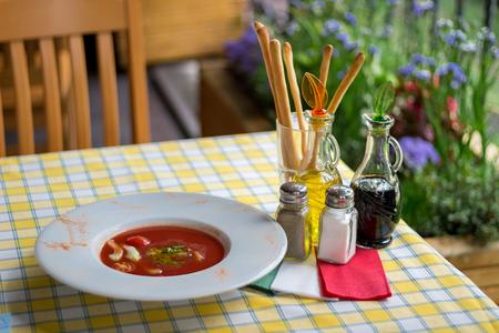 soysauce: Italian serving of gaspacho. Table set with Italian spirit