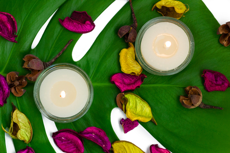 potpourri: Fresh colorful composition of two burning candles, fragrant potpourri on monstera leaf
