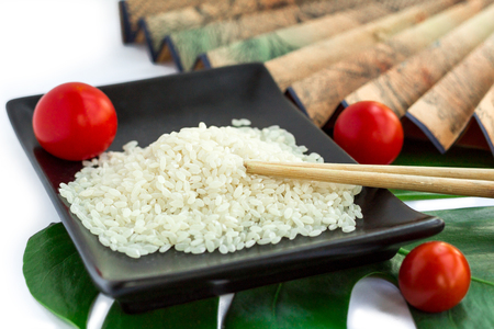 Oriental set of rice, tomatoes, chopsticks, green leaf and transp