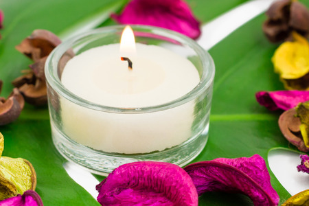 potpourri: Fresh colorful composition of burning candles fragrant potpourri on monstera leaf