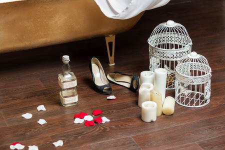 roseleaf: Romantic objects (candles, bird-cages, rose petals, shoes, empty bottle) after relaxing in bath Stock Photo