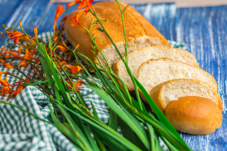sop: Fresh bread and flowers on blue wooden background and green fabric