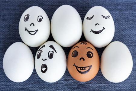 Siete huevos divertidos con caras dibujadas en dos filas, una es de color rojo, otra cara es sorprendido, sobre fondo gris
