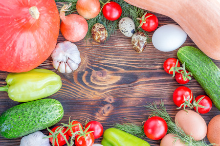 Bright Thanksgiving harvest composition of vegetables onions, cucumbers, peppers pumkin, calabash, tomatoes, garlic, eggs on dark wooden background