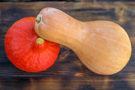 Red pumkin and yellow calabash  with hard rind laying diagonally on dark brown wooden background