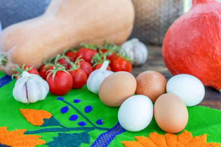 Bright Thanksgiving harvest composition of vegetables pumkin, calabash, tomatoes, garlic, eggs Stock Photo