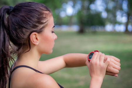 Young fitness girl checks stopwatch tracker on her wrist during running outdoor Stock Photo