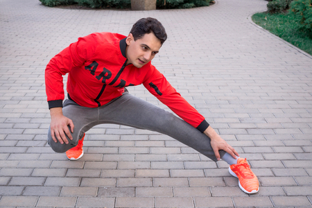 Young fitness man stretches preparing for training workout outdoor