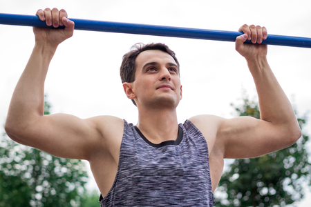 musculine: Young fitness man lifts up on horizontal bar during training workout outdoor Stock Photo