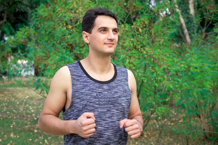 Young fitness man runs during his training workout in park outdoor