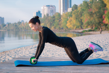 Young pretty fitness woman exercises on pier during morning training workout