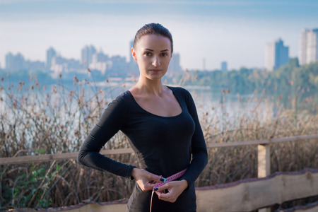 waistline: Young pretty fitness woman measures her waistline at morning river and city on backround Stock Photo