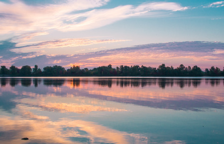 gloaming: Colorful morning sunrise reflected in mirror clear lake waters Stock Photo