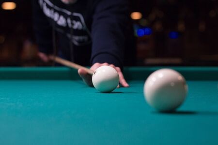 billiards cue: Russian billiards game in progress: player aims to shoot balls with cue