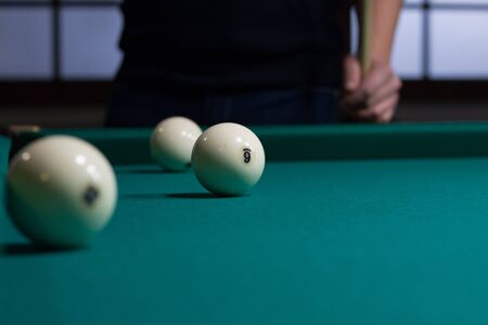 billiards cue: Close-up of Russian billiards game in process: three white balls on green game table cloth and player with cue on background