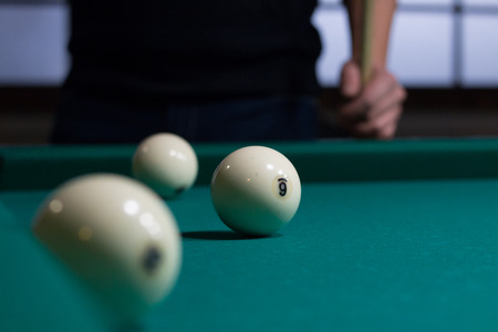 snooker tables: Close-up of Russian billiards game in process: three white balls on green game table cloth and player with cue on background