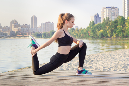 situp: Young pretty slim fitness sporty woman stretches her legs during training workout exercises outdoor at river coast in the morning