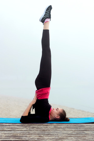 Young pretty slim fitness sporty woman does yoga exercises during training workout outdoor